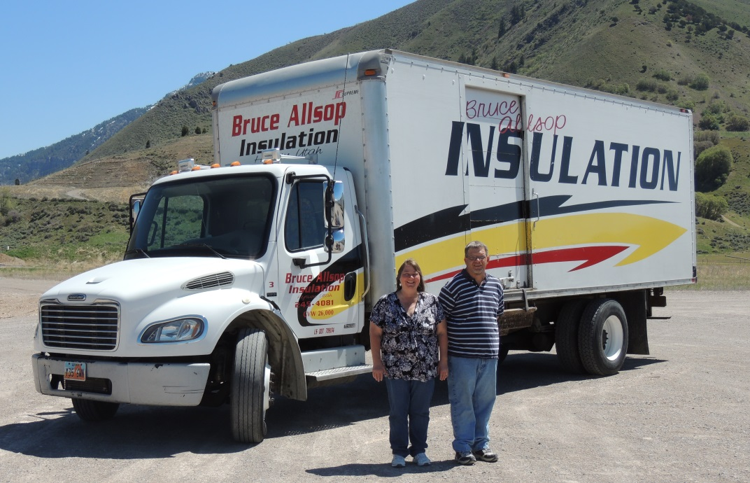 Dennis and Kim Allsop posing in front of one of the insulation installation trucks